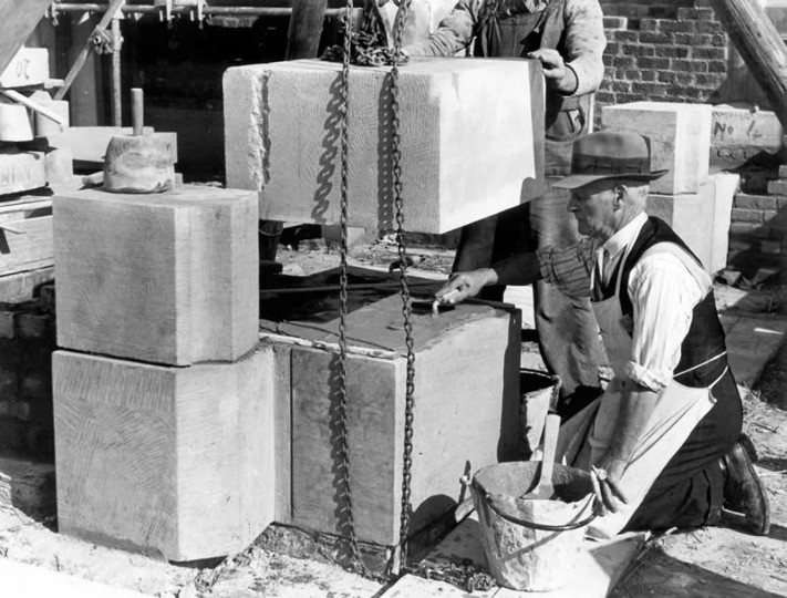 Photograph of a stonemason watching a block of stone being lowered into place